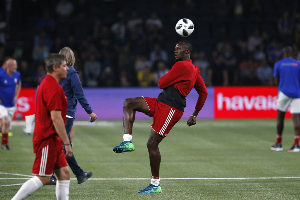 Former Olympic and Jamaican sprinter Usain Bolt controls the ball during a training session prior to the charity soccer match between members of the 1998 World Cup winning French team and a team o ...
