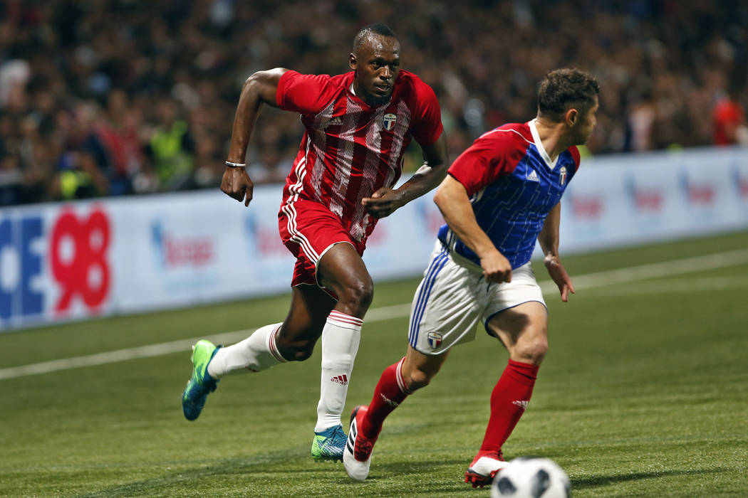 Former Olympic and Jamaican sprinter Usain Bolt, left, challenges for the ball with France's Bixente Lizarazu during a charity soccer match between members of the 1998 World Cup winning French tea ...
