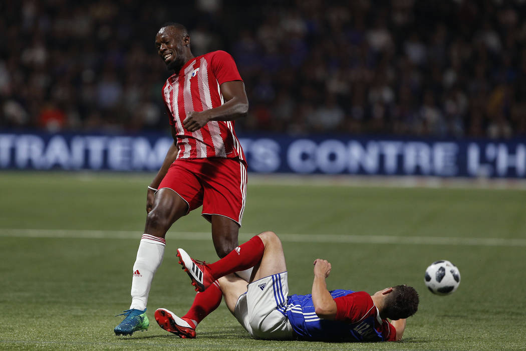 Former Olympic and Jamaican sprinter Usain Bolt, left, is tackled by Bixente Lizarazu during a charity soccer match between members of the 1998 World Cup winning French team and a team of internat ...