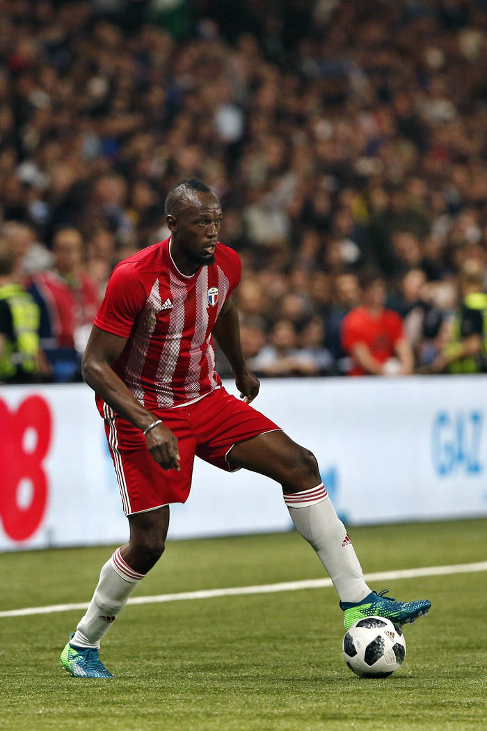 Former Olympic and Jamaican sprinter Usain Bolt controls the ball during a charity soccer match between members of the 1998 World Cup winning French team and a team of international veteran player ...