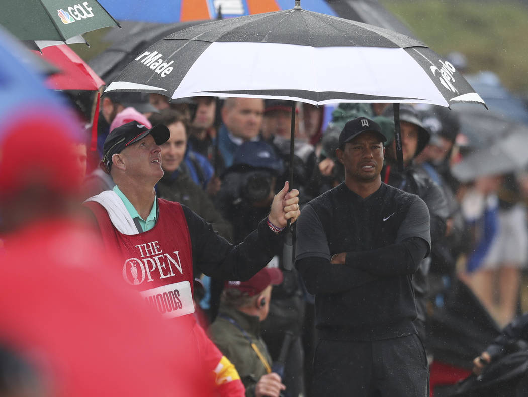 Caddie Joe Lacava shelters Tiger Woods of the US under an umbrella as he waits to play out of the rough on the 7th hole during the second round of the British Open Golf Championship in Carnoustie, ...