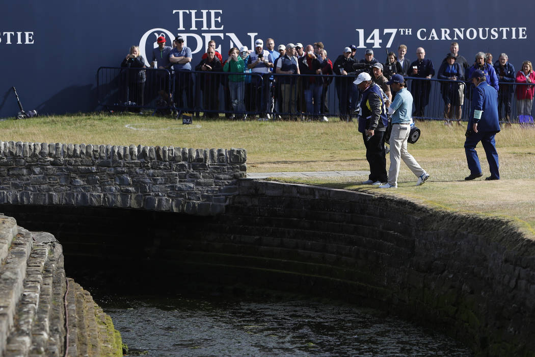 Kevin Kisner of the US talks to officials after hitting the ball into the water on the 18th hole during the second round of the British Open Golf Championship in Carnoustie, Scotland, Friday July ...