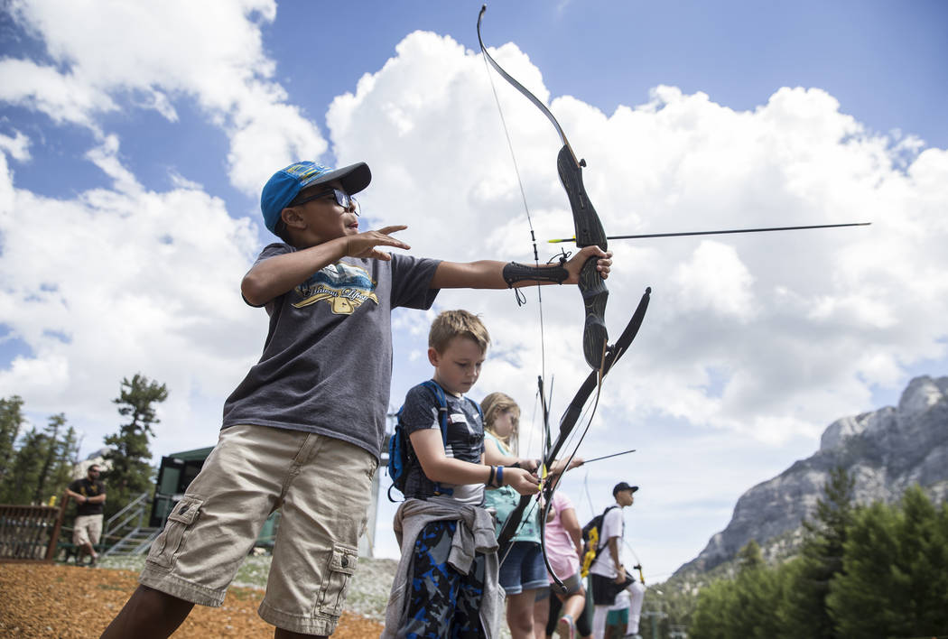 James Mendoza, left, practices his archery skills during Youth Adventure Day at Lee Canyon on Friday, July 20, 2018, in Las Vegas. Benjamin Hager Las Vegas Review-Journal @benjaminhphoto