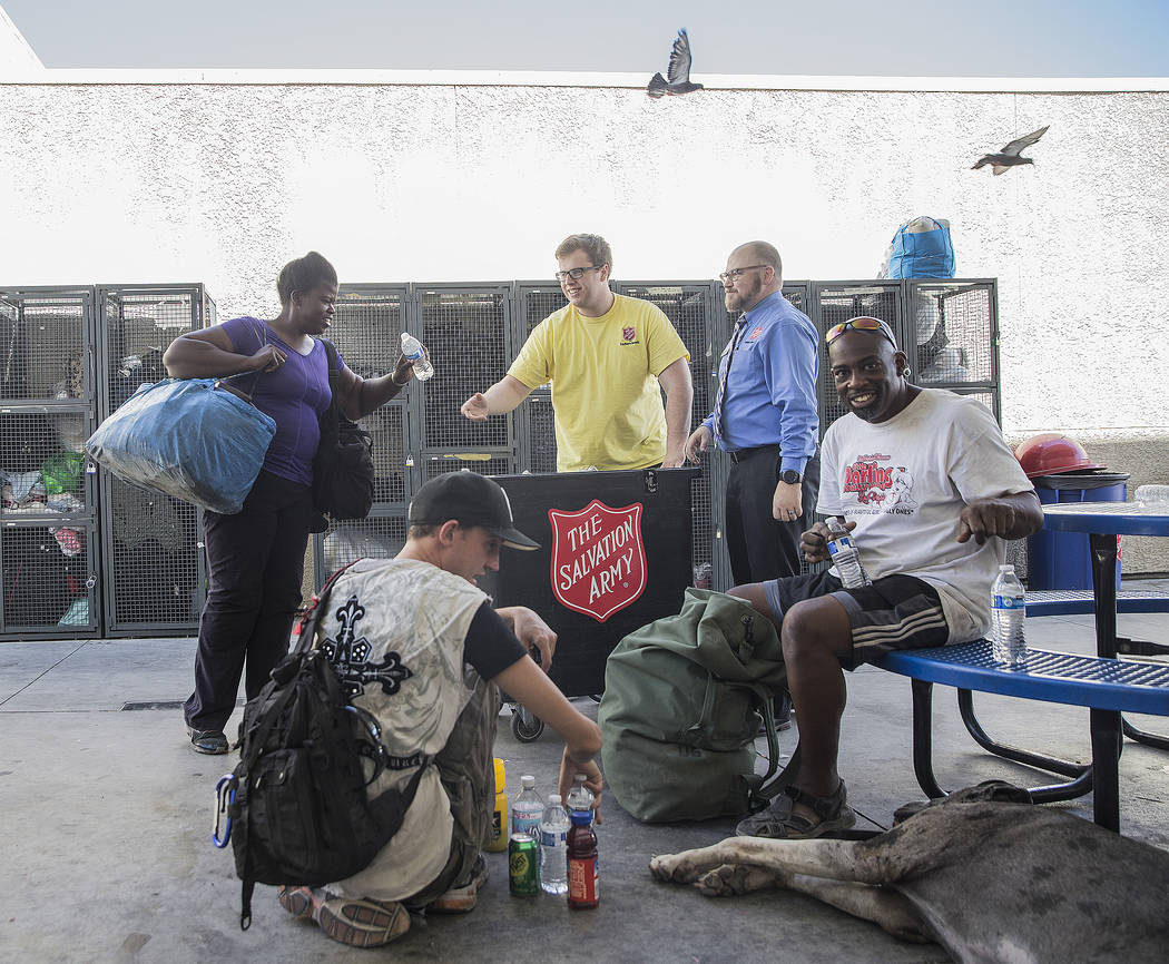 Shelter monitor Boston Brimhall, middle, and homeless services coordinator Ryan McDonald hand out water at a cooling station at The Salvation Army on Thursday, July 5, 2018, in Las Vegas. Benjamin ...