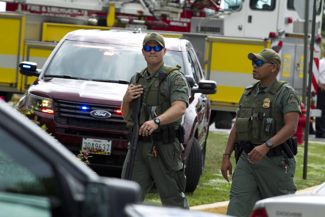 In this June 28, 2018 file photo, Maryland police officers patrol the area after multiple people were shot at at The Capital Gazette newspaper in Annapolis, Md. (AP Photo/Jose Luis Magana, File)