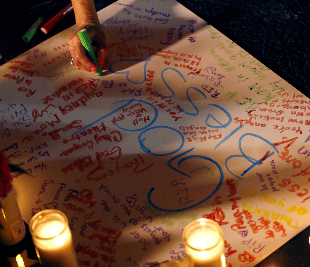 A woman writes a message during a candlelight vigil in the parking lot of Ride the Ducks Friday, July 20, 2018, in Branson, Mo. One of the company's duck boats capsized Thursday night resulting in ...