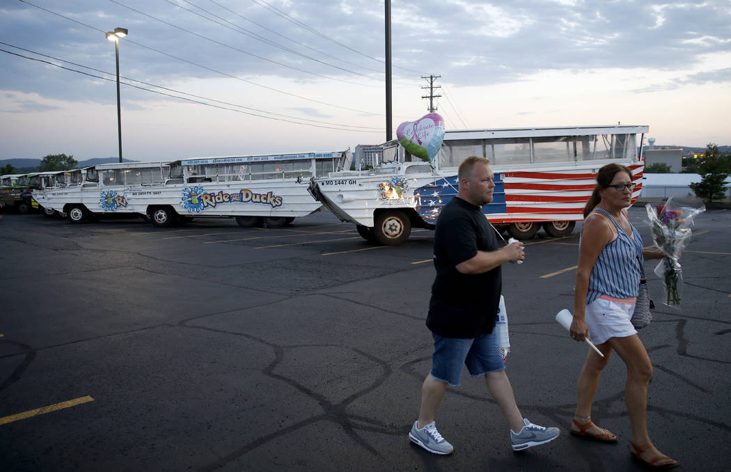 People walk past parked duck boats as the walk to a candlelight vigil in the parking lot of Ride the Ducks Friday, July 20, 2018, in Branson, Mo. One of the company's duck boats capsized Thursday ...