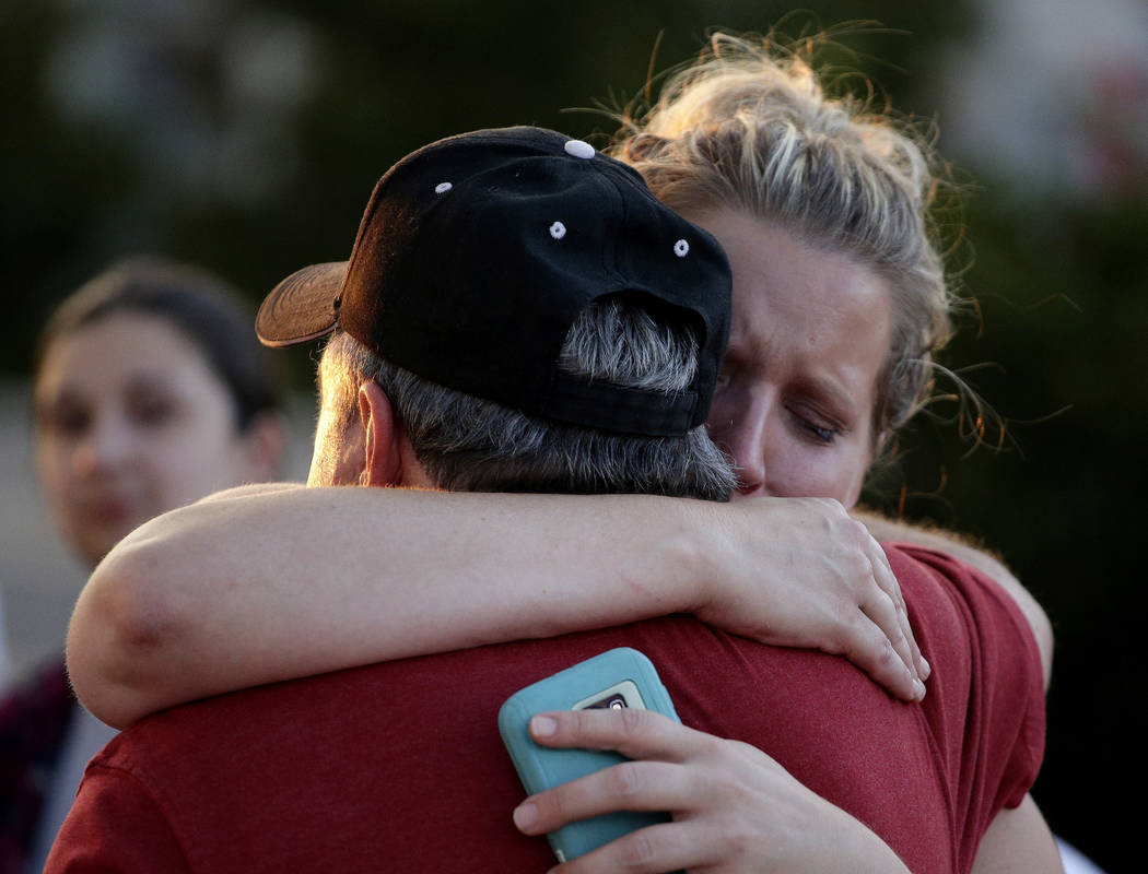 Rachel Riutzel hugs Russ McKay as he looks at a makeshift memorial for his friends before a candlelight vigil in the parking lot of Ride the Ducks Friday, July 20, 2018 in Branson, Mo. One of the ...