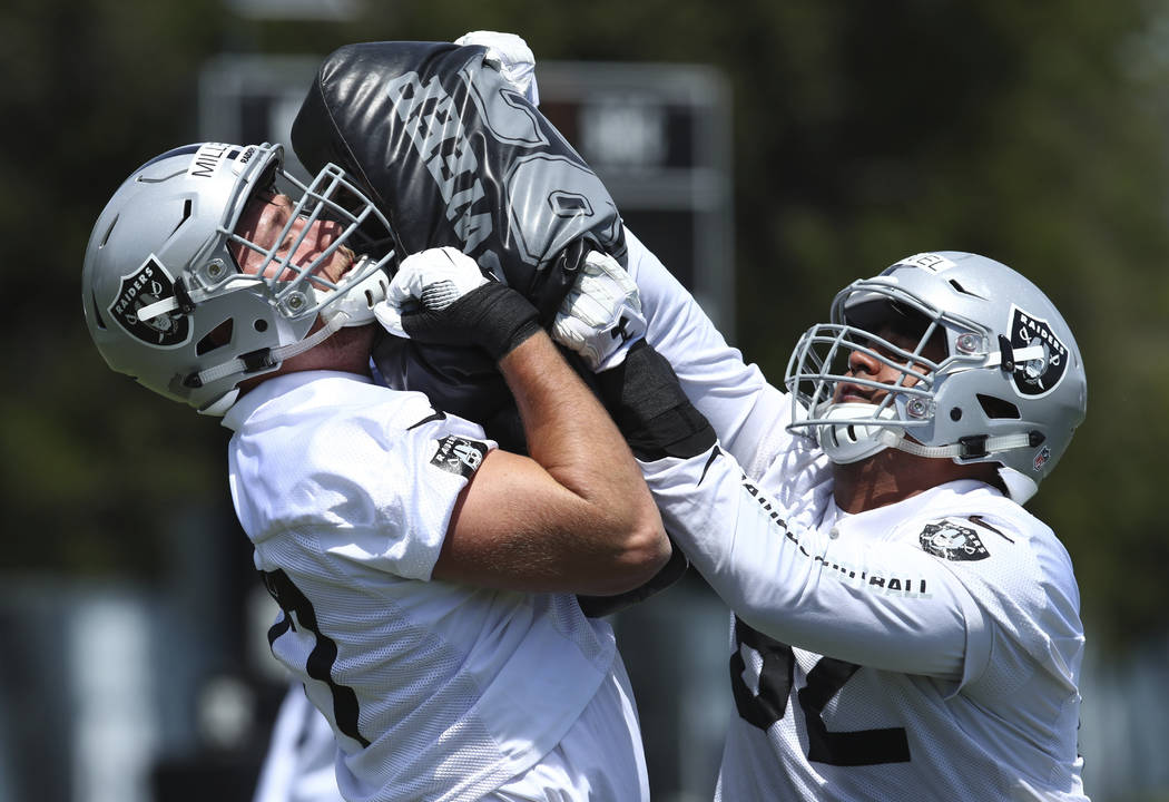 Oakland Raiders' Kolton Miller, left, blocks during an NFL football practice on Friday, May 4, 2018, at the team's training facility in Alameda, Calif. (AP Photo/Ben Margot)