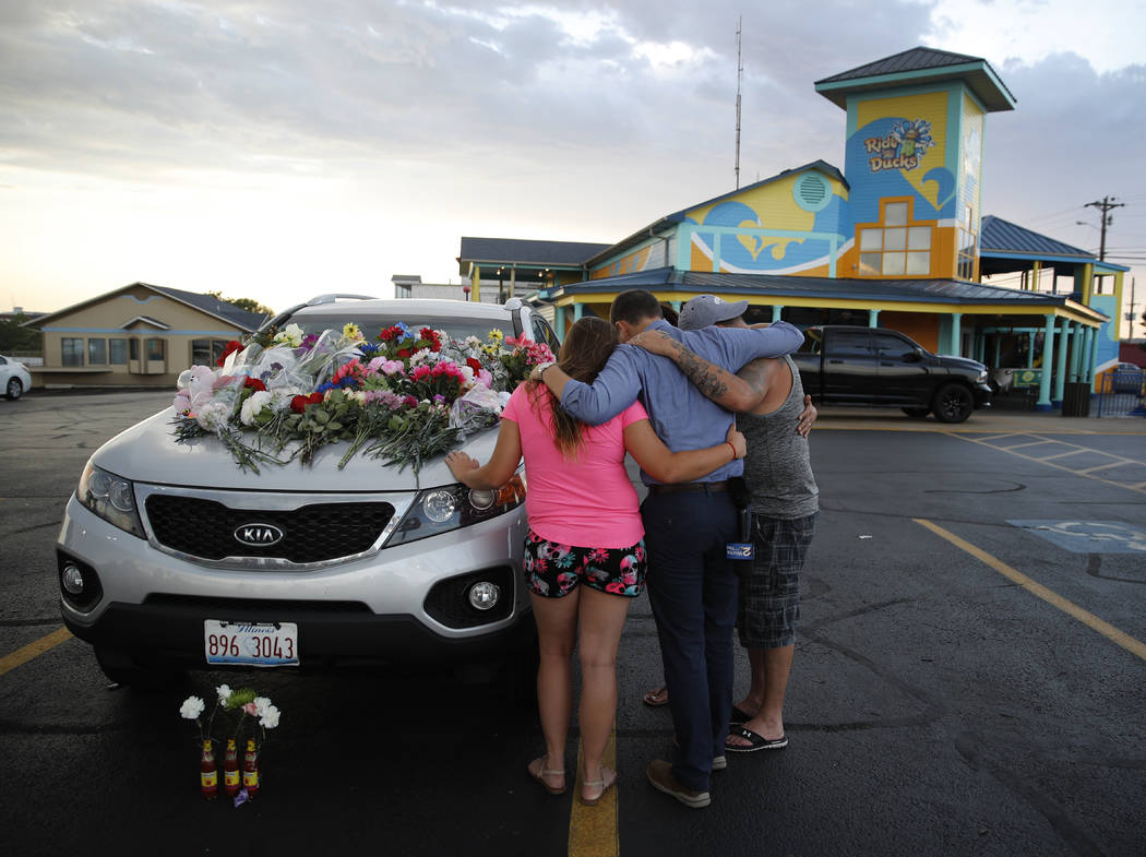 People pray by a car thought to belong to a victim of Thursday's boating accident before a candlelight vigil in the parking lot of Ride the Ducks Friday, July 20, 2018, in Branson, Mo. One of the ...