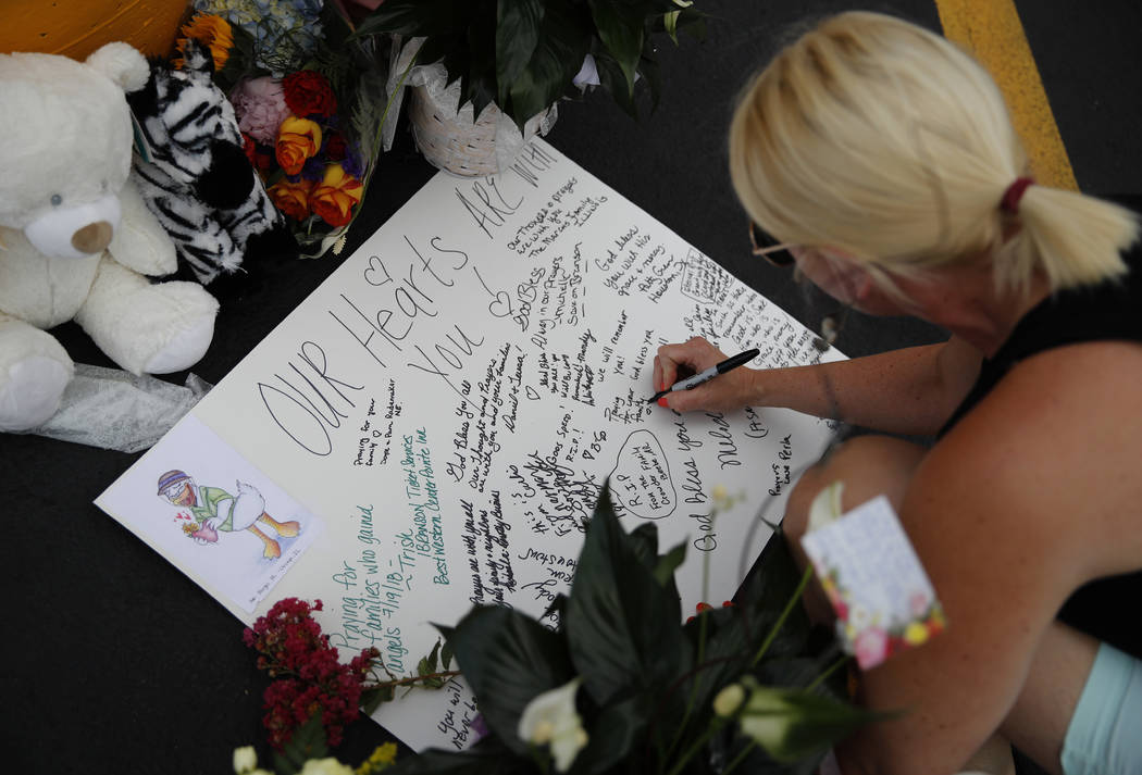 A woman writes a message during a candlelight vigil in the parking lot of Ride the Ducks Friday, July 20, 2018 in Branson, Mo. One of the company's duck boats capsized Thursday night resulting in ...