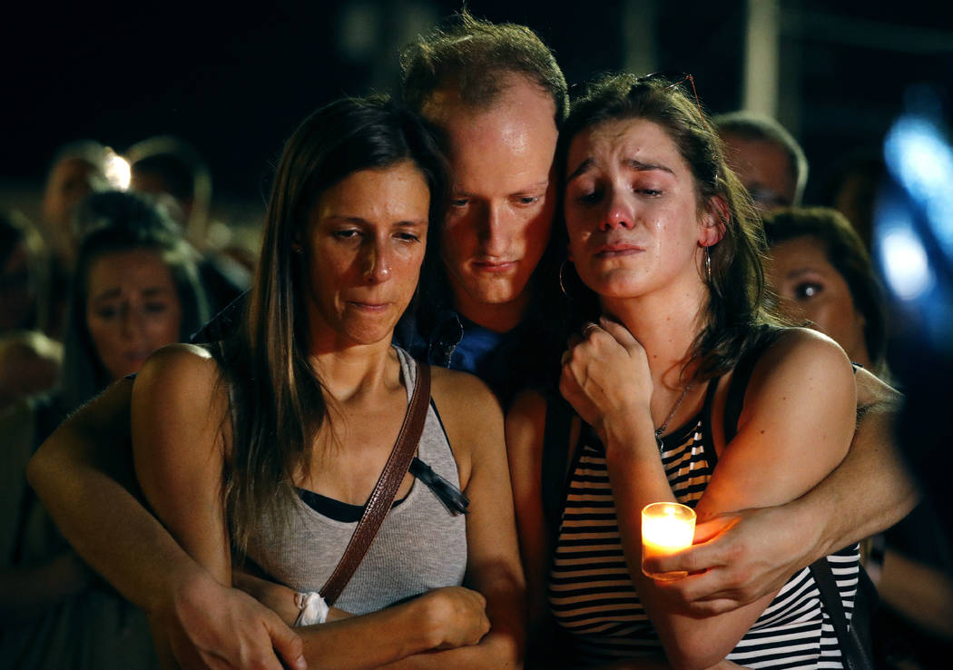 Mallory Cunningham, left, Santino Tomasetti, center, and Aubrey Reece attend a candlelight vigil in the parking lot of Ride the Ducks Friday, July 20, 2018, in Branson, Mo. One of the company's du ...