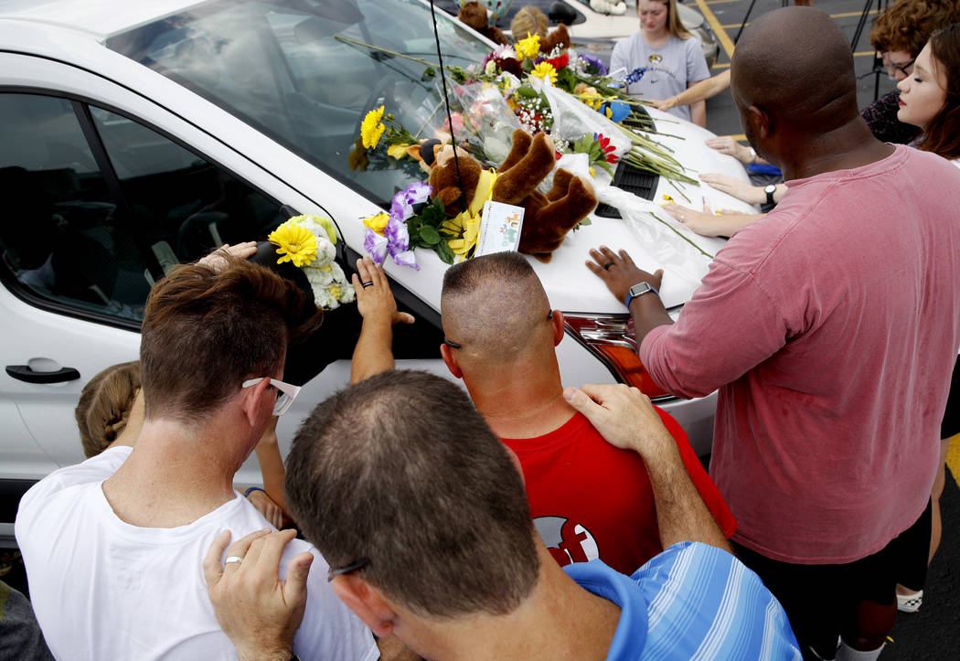 People pray around a van believed to belong to victims of a duck boat accident in the parking lot of the business running the boat tours Friday, July 20, 2018 in Branson, Mo. The country-and-weste ...
