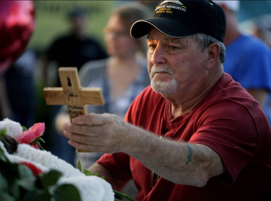 Russ McKay looks at a cross left in a makeshift memorial for his friends before a candlelight vigil in the parking lot of Ride the Ducks Friday, July 20, 2018, in Branson, Mo. One of the company's ...
