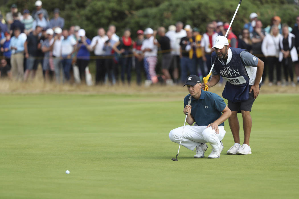 Jordan Spieth of the US and his caddie Michale Greller line up a putt on the 9th hole during the third round of the British Open Golf Championship in Carnoustie, Scotland, Saturday July 21, 2018. ...