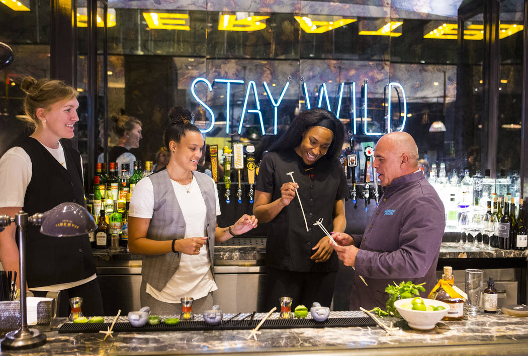 Mixologist Tony Abou-Ganim, right, hands swizzle sticks to Las Vegas Aces players, from left, Carolyn Swords, Kayla McBride and Kelsey Bone at Libertine Social in the Mandalay Bay in Las Vegas on ...
