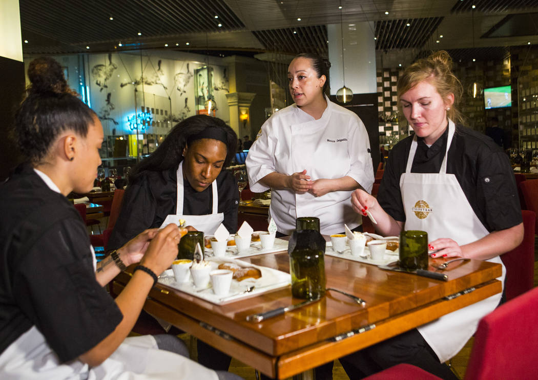 Monica Delgadillo, pastry chef at Stripsteak, third from left, talks with Las Vegas Aces players, from left, Kayla McBride, Kelsey Bone and Carolyn Swords after making beignets in the Mandalay Bay ...