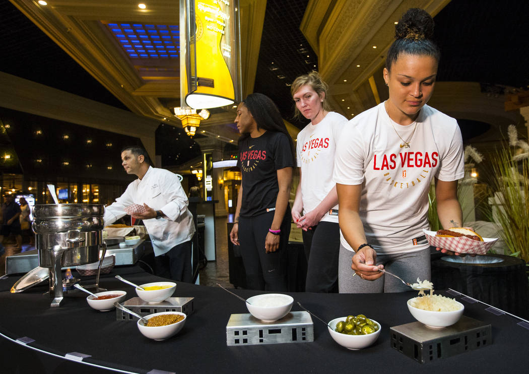 "Las Vegas Aces player Kayla McBride, right, adds toppings to an ""Aces Dog,"" a bacon-wrapped, mesquite-smoked beef dog in an herb garlic buttered bun with Jack Daniel's BBQ sauce, in the ..."