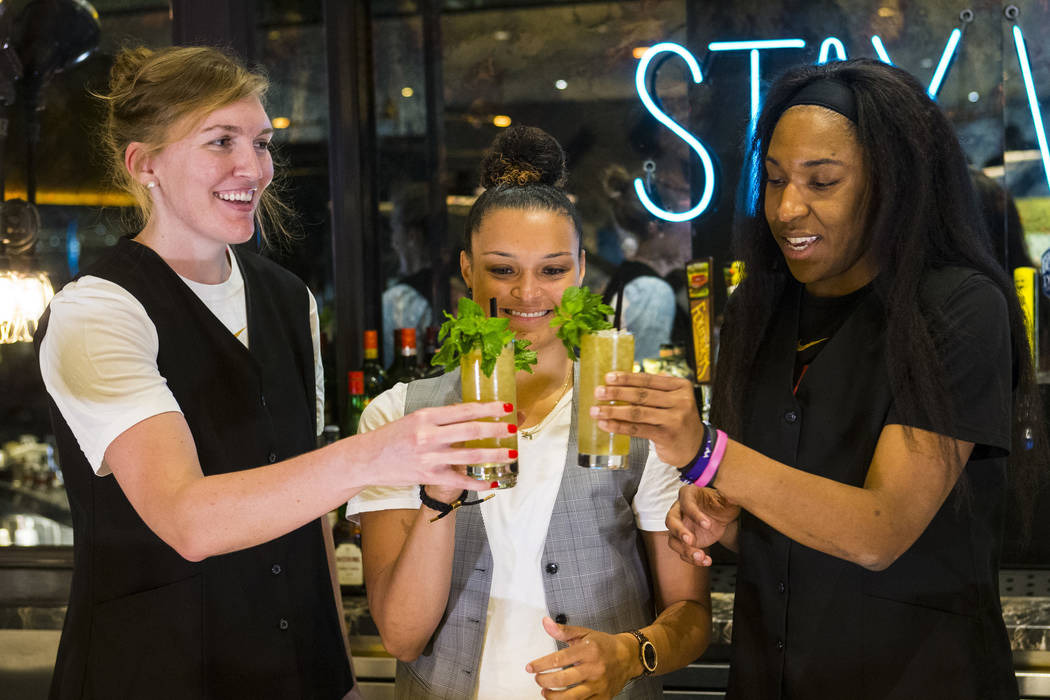 Las Vegas Aces players, from left, Carolyn Swords, Kayla McBride and Kelsey Bone toast after making a Summer Swizzle cocktail with the help of mixologist Tony Abou-Ganim. not pictured, at Libertin ...