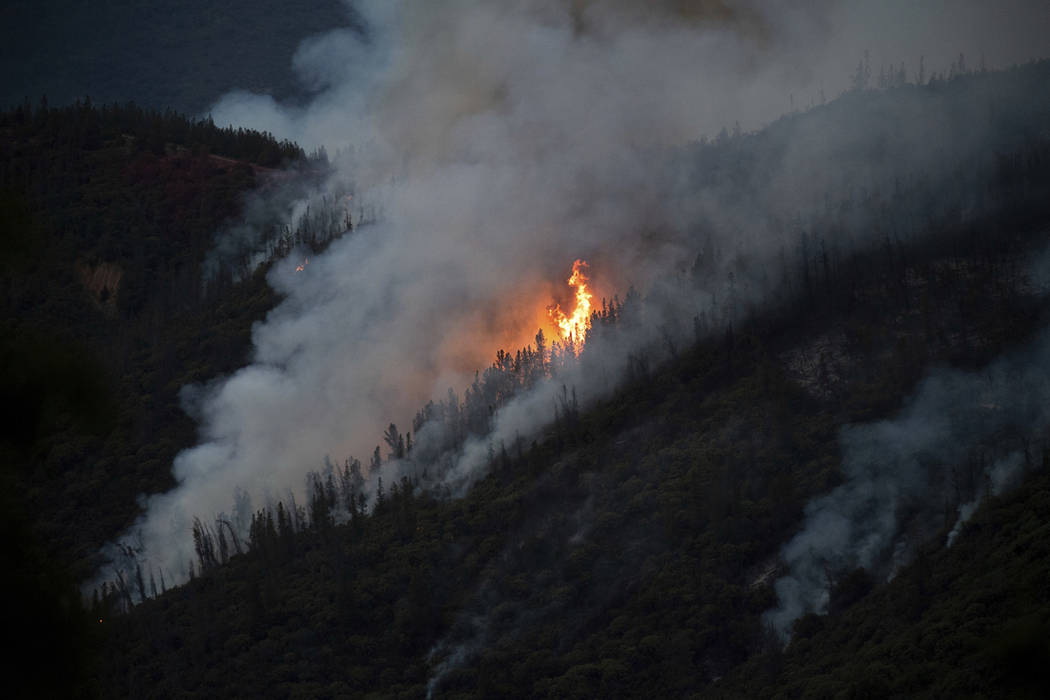In this Sunday, July 15, 2018, file photo, flames from the Ferguson Fire burn down a hillside in unincorporated Mariposa County Calif., near Yosemite National Park. (AP Photo/Noah Berger, File)