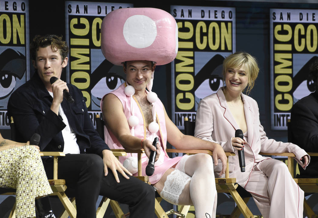 "Callum Turner, from left, Ezra Miller, dressed in a Toadette costume from the Super Mario Bros. video game franchise, and Alison Sudol attend the Warner Bros. Theatrical panel for ""Fantastic ..."