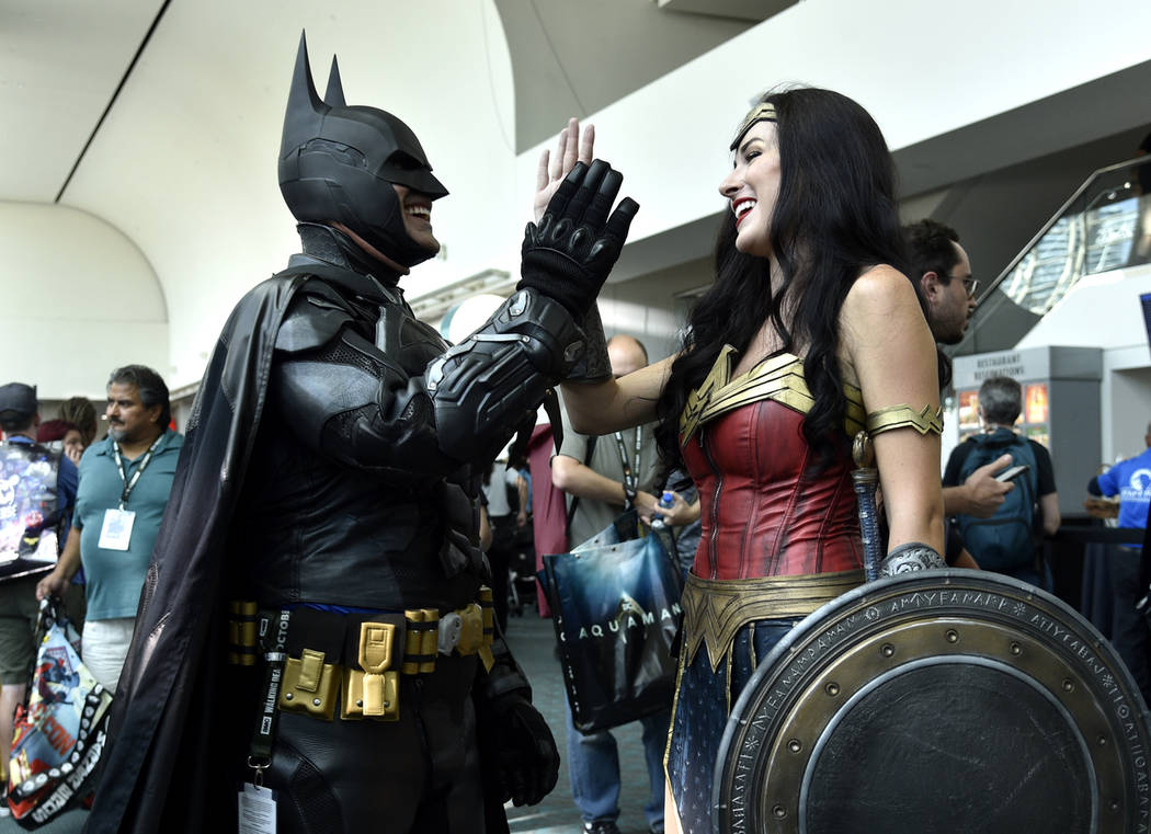 Armando Abarca, left, dressed as Batman, and Jessica Rose Davis, dressed as Wonder Woman, of Los Angeles, high five each other as they attend day one of Comic-Con International on Thursday, July 1 ...