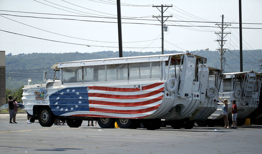 People look at idled duck boats in the parking lot of Ride the Ducks Saturday, July 21, 2018 in Branson, Mo. One of the company's duck boats capsized Thursday night resulting in several deaths on ...