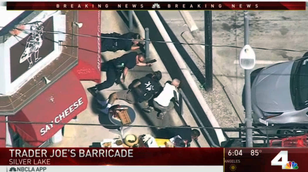 In this image from video provided by KNBC-TV, police and civilians take cover near a Trader Joe's supermarket in the Silver Lake district of Los Angeles Saturday, July 21, 2018. (KNBC-TV via AP)