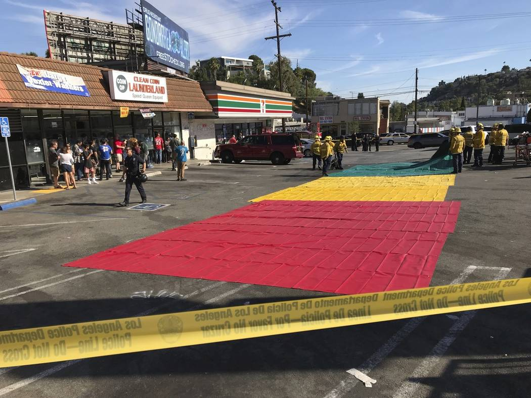 Police and rescue personnel set up a triage area a block away from a Trader Joe's where a suspect has barricaded himself inside Saturday, July 21, 2018, in Los Angeles. (AP Photo/Damian Dovarganes)