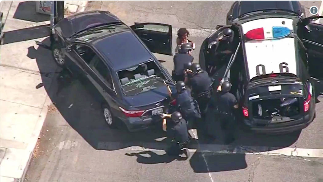 In this image from video provided by KNBC-TV, Los Angeles Police officers remove a passenger from a car that crashed after a pursuit with the driver who ran into a nearby Trader Joe's supermarket ...