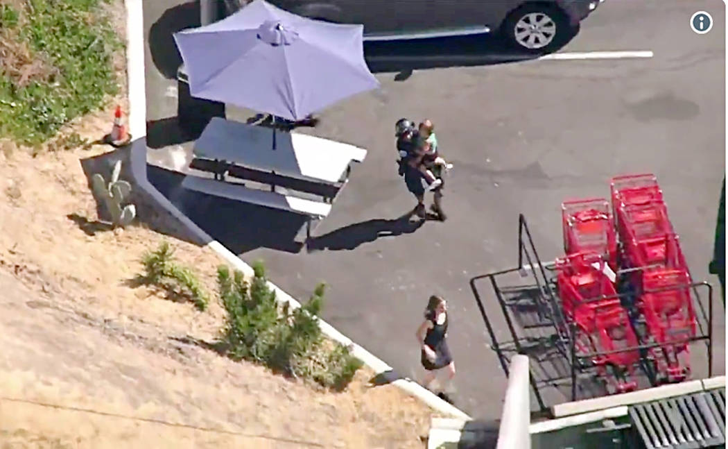 In this image from video provided by KNBC-TV, a Los Angeles Police officer carries a child as a woman runs ahead of them near a Trader Joe's supermarket in the Silver Lake district of Los Angeles ...