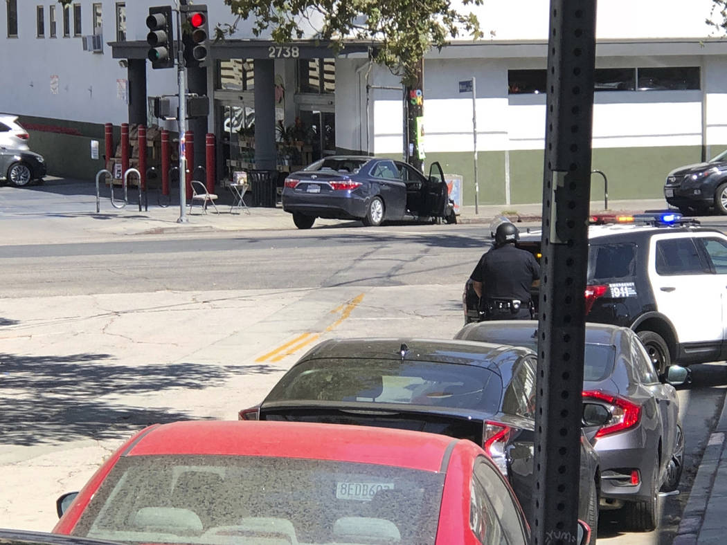 In this photo provided by Christian Dunlop, police officers stand guard near a crashed vehicle outside a Trader Joe's store in the Silver Lake neighborhood of Los Angeles on Saturday, July 21, 201 ...