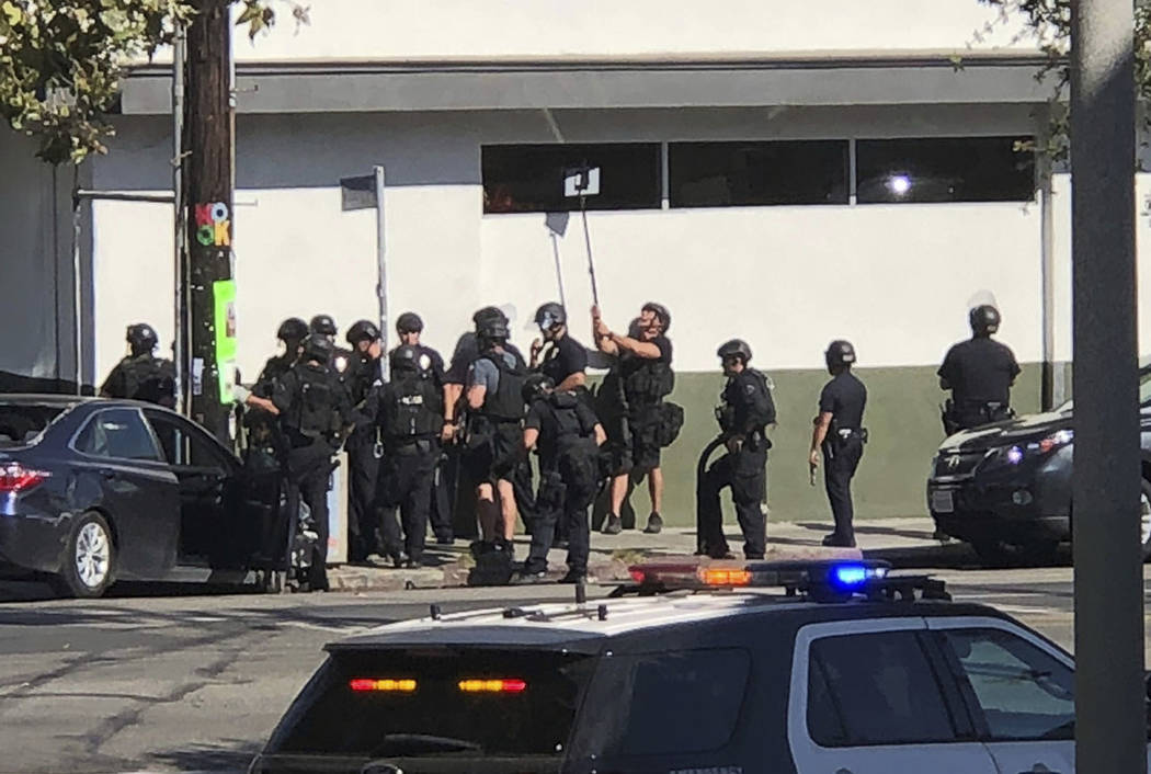 In this photo provided by Christian Dunlop, police officers use a mirror to see inside a Trader Joe's store in the Silver Lake neighborhood of Los Angeles on Saturday, July 21, 2018. (Christian Du ...
