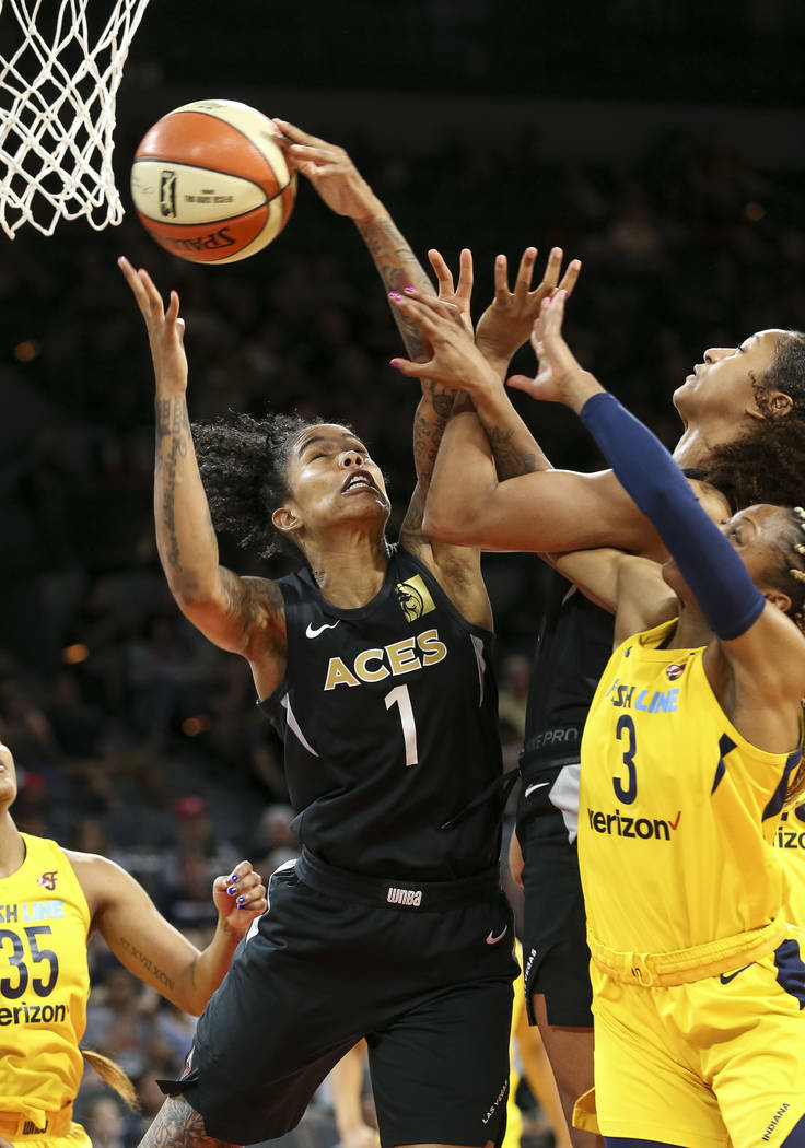 Las Vegas Aces forward Tamera Young (1) pulls in the rebound over Indiana Fever guard Tiffany Mitchell (3) and teammate Jaime Nared (31) during the second half of a WNBA basketball game at the Man ...