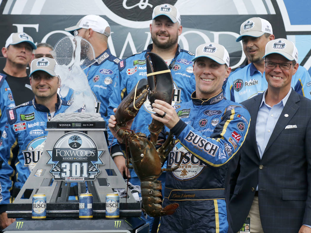 Kevin Harvick smiles as he holds up a large lobster in victory lane after winning the NASCAR Cup Series auto race Sunday, July 22, 2018, at New Hampshire Motor Speedway in Loudon, N.H. (AP Photo/M ...
