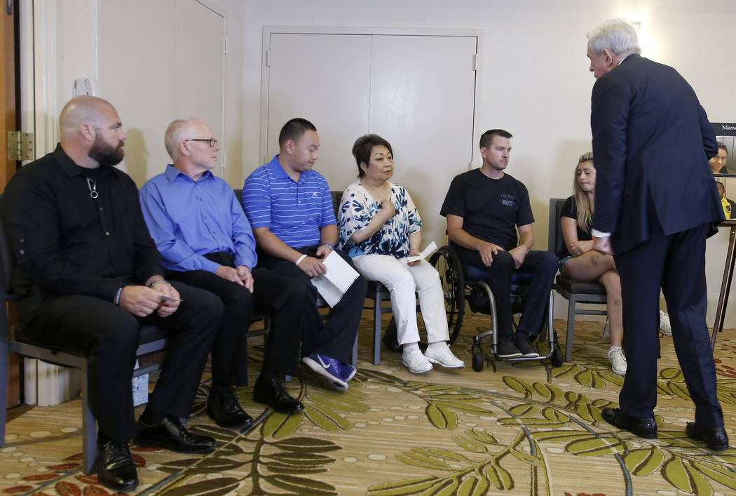 Attorney Mark P. Robinson, right, talks with shooting victims and family members who lost loved ones in the Oct. 1, 2017, Las Vegas shooting, talks about MGM's decision, at a news conference in Ne ...