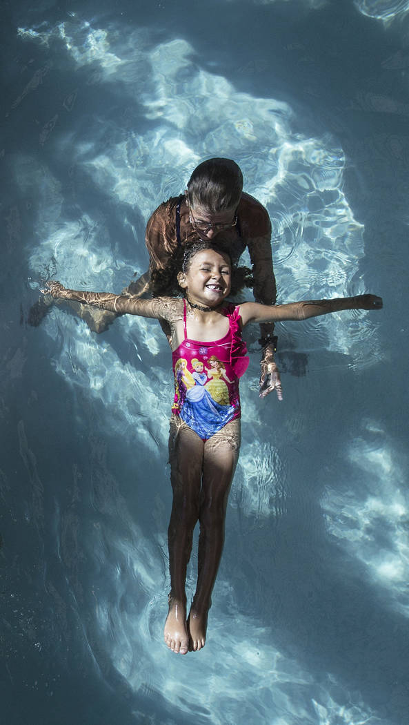 Alynah Lawton, 6, practices floating with the help of water safety instructor Lisa Peschi during swim class at the Hollywood Aquatic Center on Monday, July 23, 2018, in Las Vegas. Benjamin Hager L ...