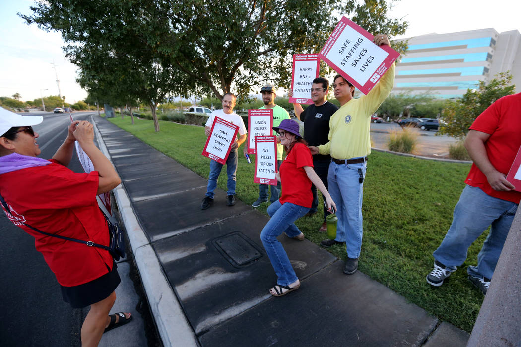 Toni Stockman, left, takes a photo of nurses and supporters affiliated with the Nevada chapter of the national Nurses Organizing Committee prepare to protest outside MountainView Hospital in Las V ...