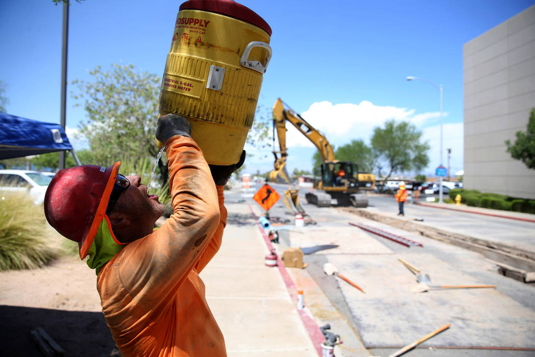Todd Hassey takes a water break while laying pipe under Basic Road at Lynn Street near Henderson City Hall Tuesday, July 24, 2018. (K.M. Cannon/Las Vegas Review-Journal) @KMCannonPhoto