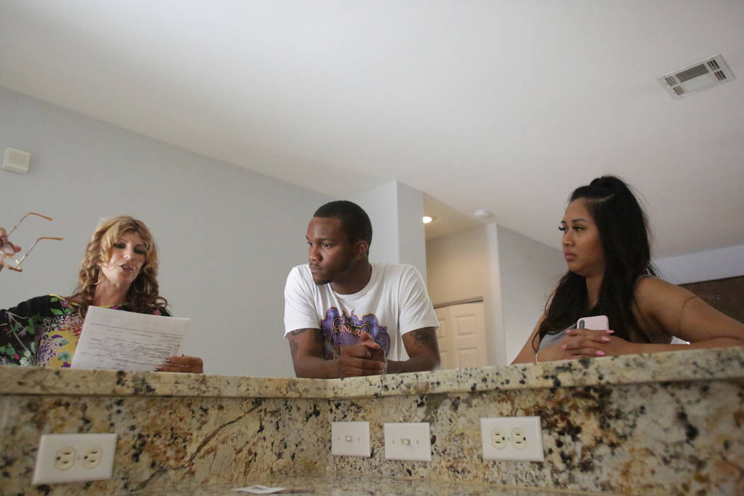 Darrius Mathis, center, and Kayte Fernandez go over the details of a rental home in Summerlin with their real estate agent Karen Feldman, left, of America's Choice Realty on Friday, July 20, 2018. ...