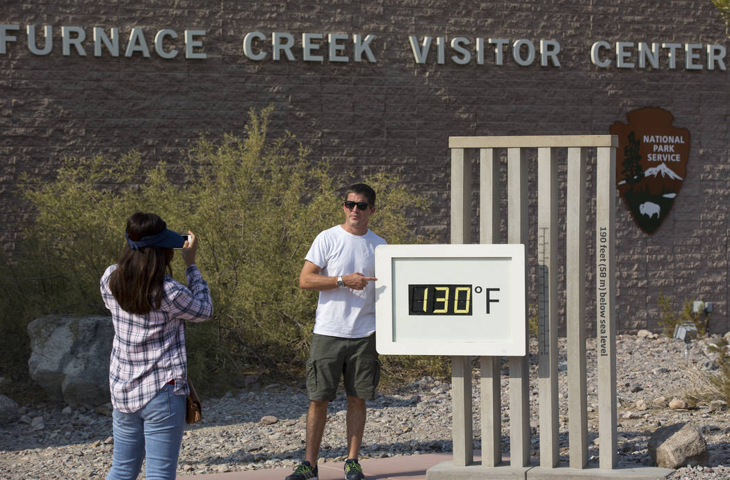 Las Vegas residents Cory Perez, left, and Jon Bach take photos at the Furnace Creek Visitor Center thermometer in Death Valley National Park, Calif., Thursday, July 26, 2018. Richard Brian Las Veg ...