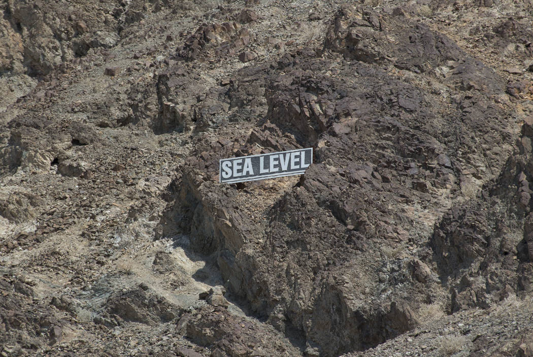 A sign marking sea level is on the cliff from Badwater Basin, 282 feet below sea level, in Death Valley National Park, Calif., on Thursday, July 26, 2018. Richard Brian Las Vegas Review-Journal @v ...