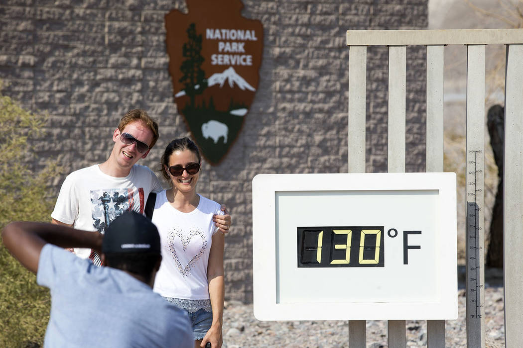 A couple poses at the Furnace Creek Visitor Center thermometer in Death Valley National Park, Calif., Thursday, July 26, 2018.The official temperature at the park rose to 127 on Thursday, although ...