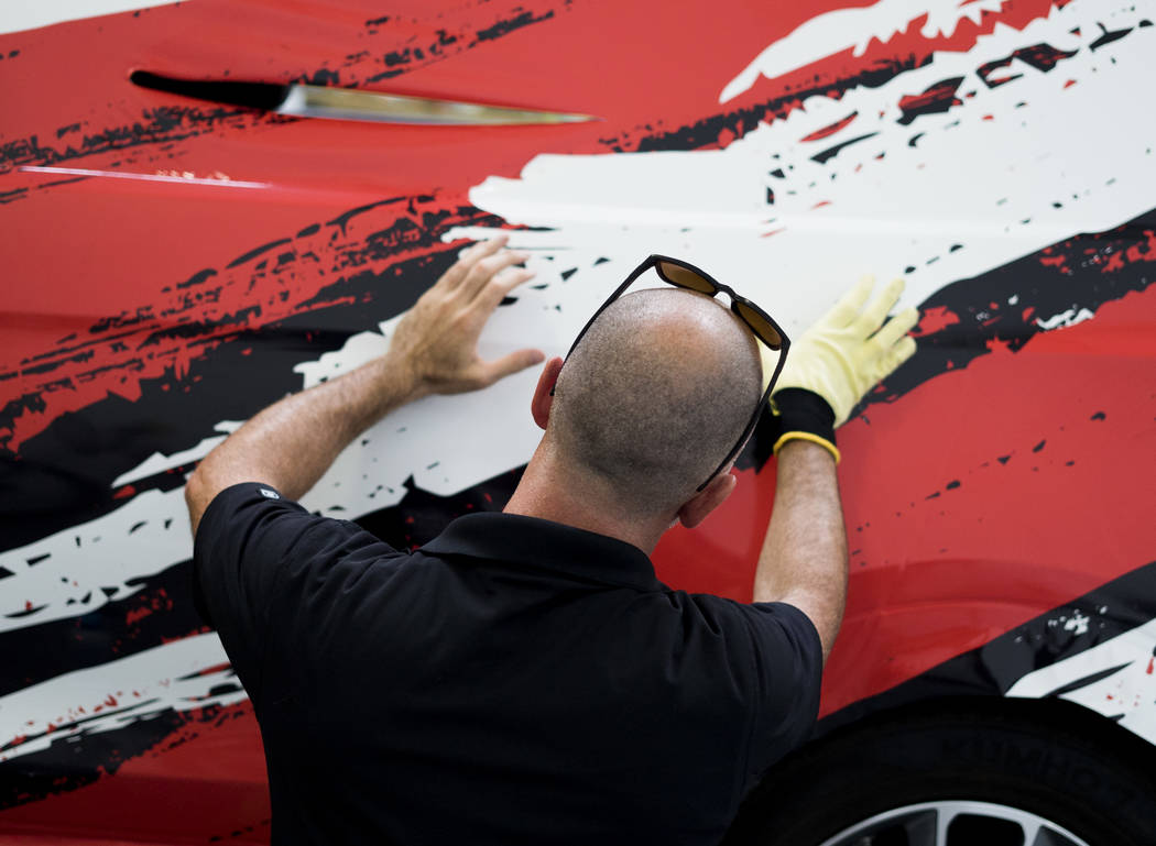 Elliott Nail, co-owner of5150 Wraps, prepares a vehicle for the company's first neon wrap installation in Henderson, Monday, July 23, 2018. (Marcus Villagran/Las Vegas Review-Journal) @broke ...