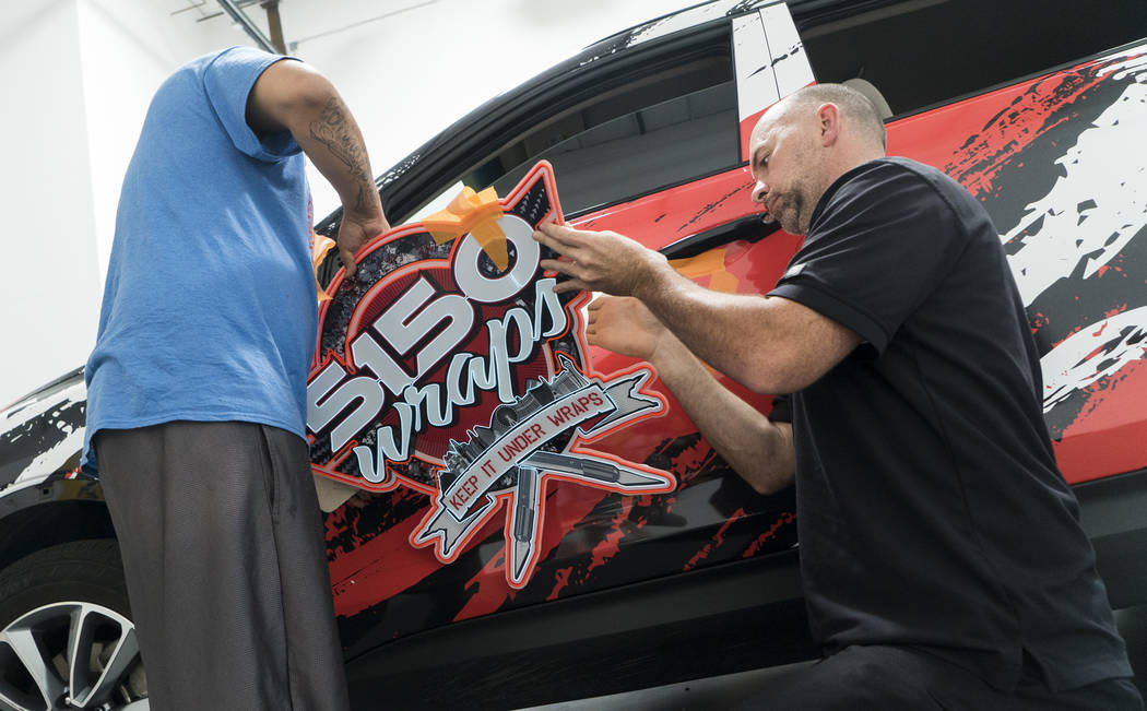 Ruben Garcia, installer at 5150 Wraps, and Elliott Nail, co-owner at 5150 Wraps, install the company's first neon wrap installation in Henderson, Wednesday, July 25, 2018. (Marcus Villagran/Las Ve ...