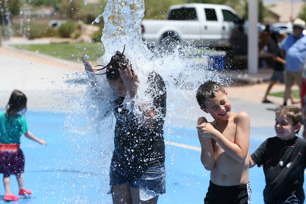 Calicia Marquez, left, 12, and Colby Drohn, 7, play on the splash pad at Gilcrease Brothers Park in Las Vegas, Saturday, June 23, 2018. Erik Verduzco Las Vegas Review-Journal @Erik_Verduzco