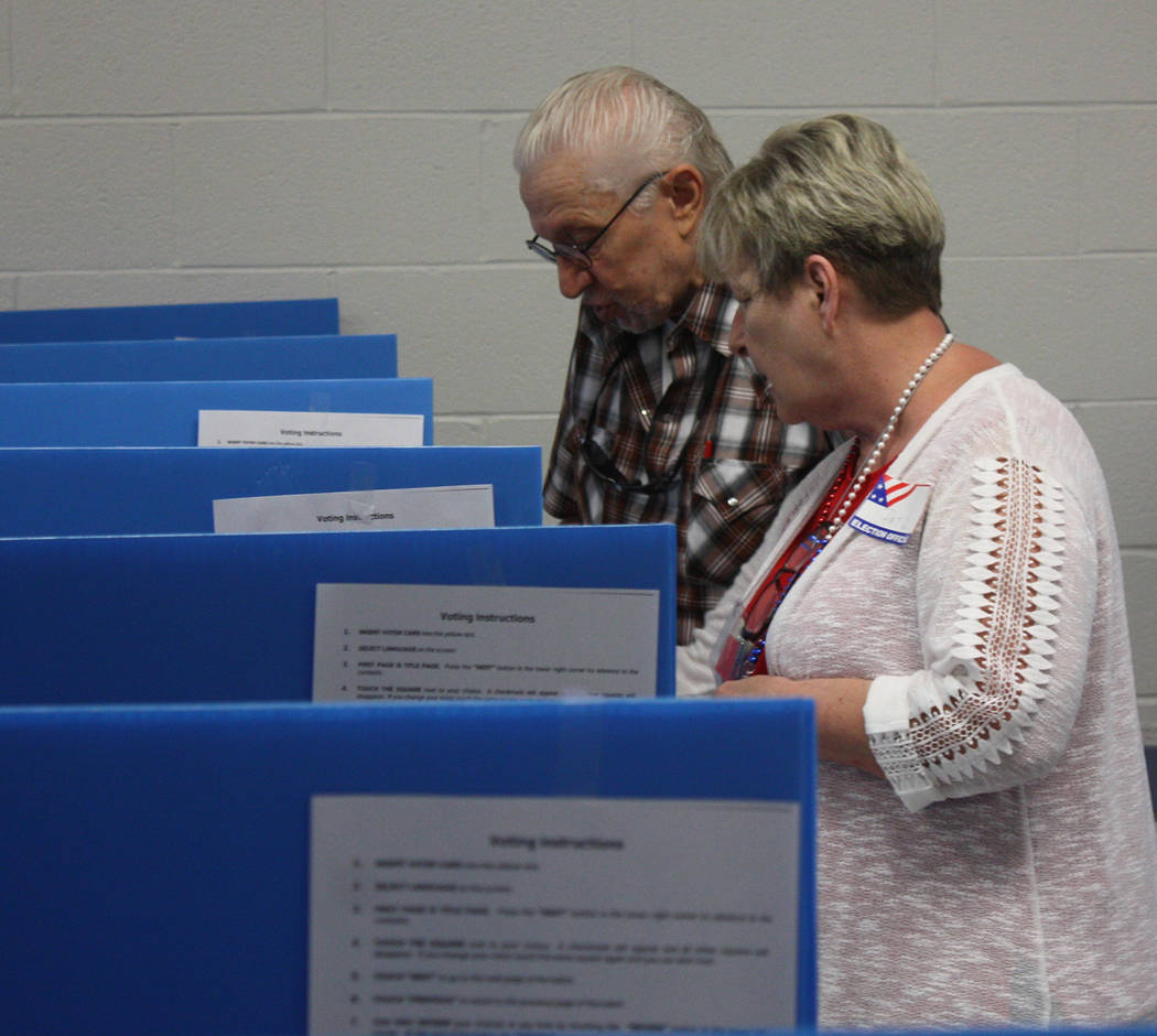 An election site worker is pictured assisting a local man with voting machines. Robin Hebrock/Pahrump Valley Times