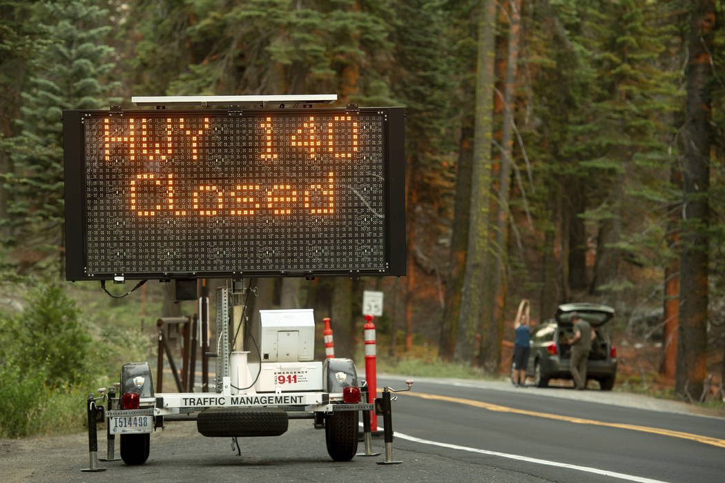 A sign announces a highway closure in Yosemite National Park, Calif., on Tuesday, July 24, 2018, as the Ferguson Fire burns nearby. Highway 140 has been closed more than a week as firefighters wor ...