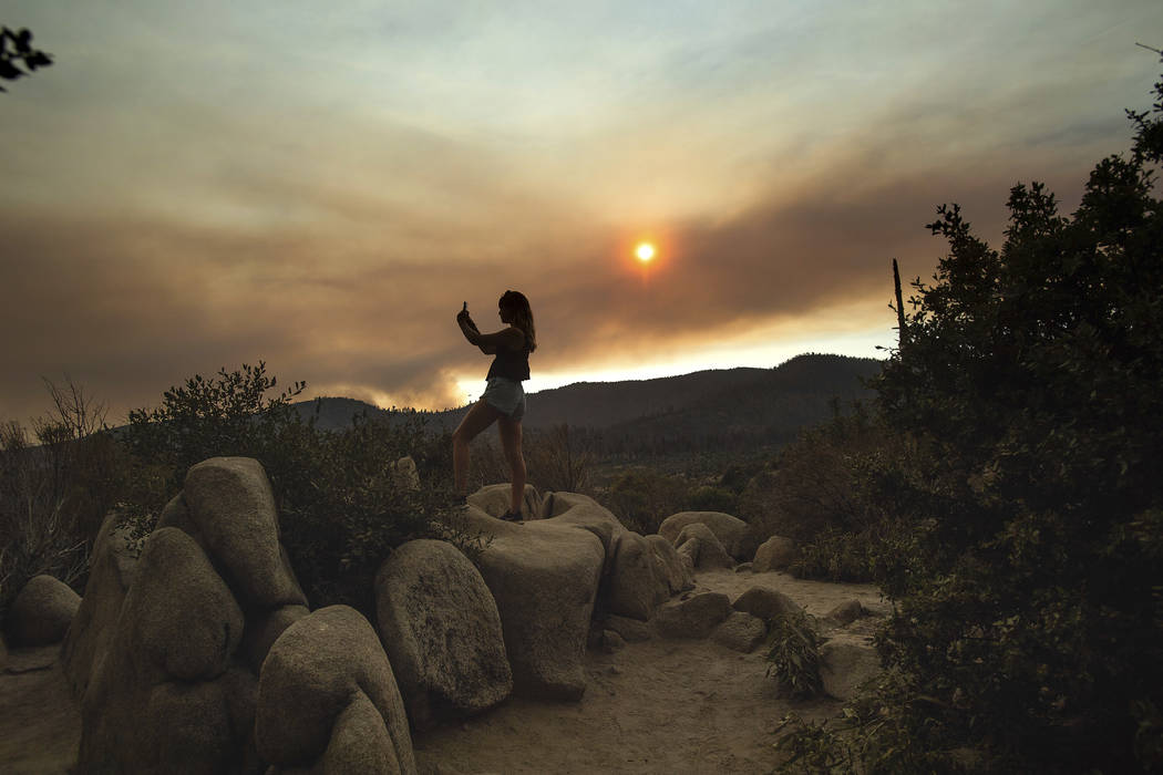 Mara Schumann photographs a plume of smoke from the Ferguson Fire in Yosemite National Park, Calif., on Tuesday, July 24, 2018. Parts of the park, including Yosemite Valley, will close Wednesday a ...