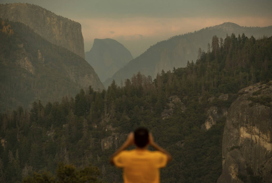 Francisco Avendano, visiting from Madrid, Spain, photographs Half Dome as smoke from the Ferguson Fire hangs over Yosemite National Park, Calif., on Tuesday, July 24, 2018. Parts of the park, incl ...